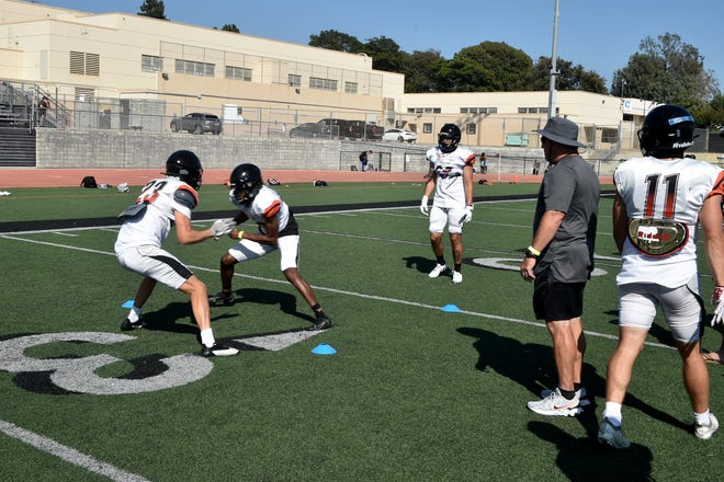 Head coach Steve Mooshagian (second from right) watches over a drill during the Ventura College football team's practice on Thursday, Aug. 26, 2021.