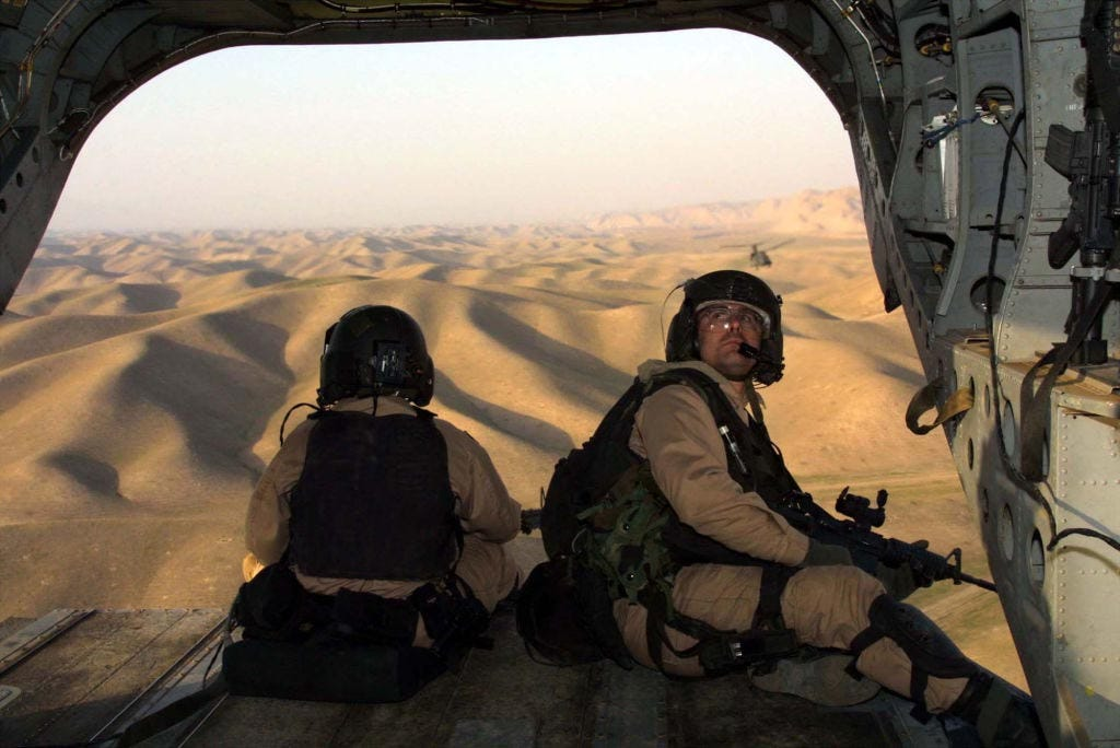 Flying over hills into Afghanistan from Tajikistan, U.S. special operations soldiers keep watch from the back end of a Chinook helicopter in November 2001.