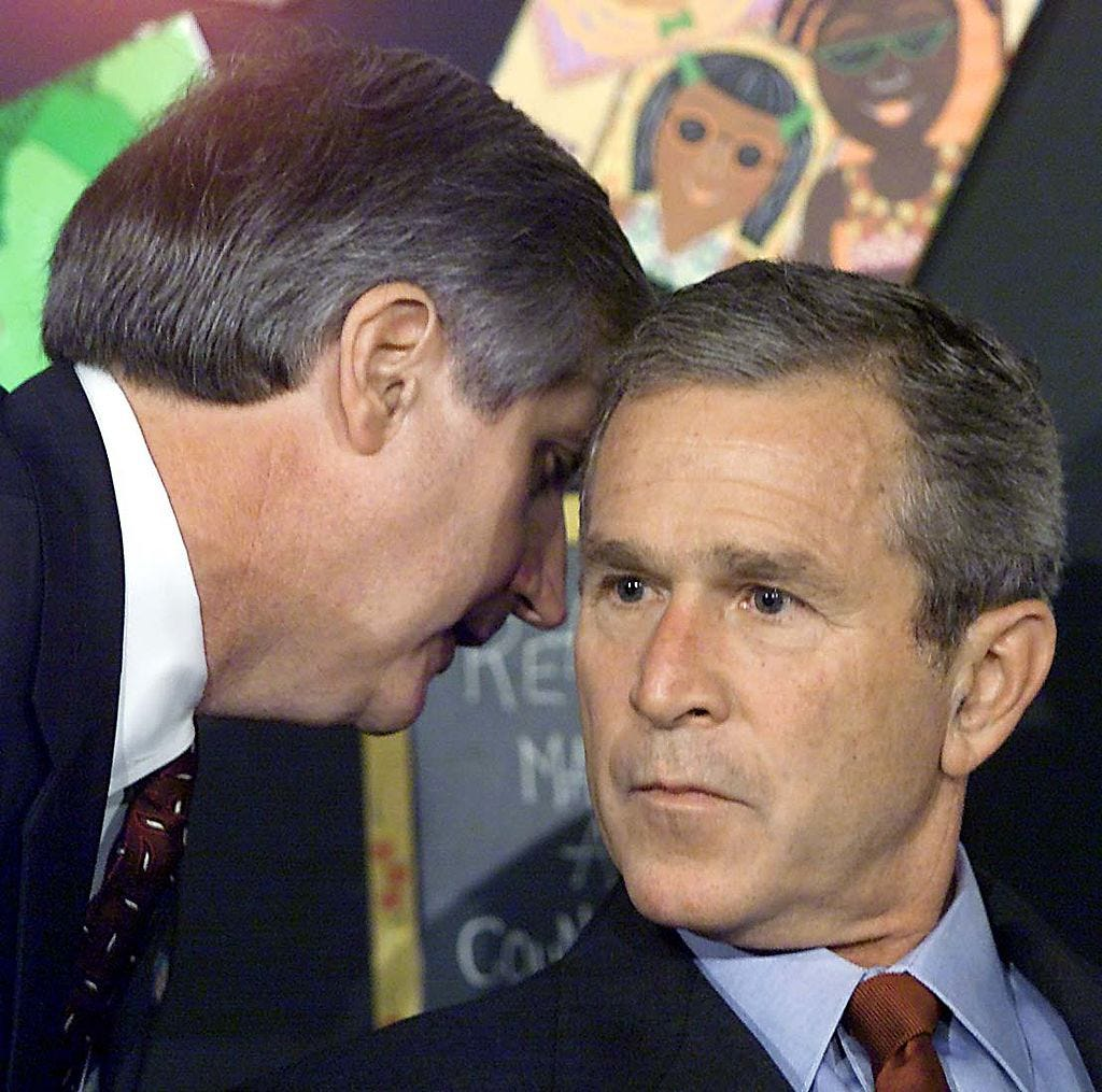 President George W. Bush is informed by chief of staff Andy Card of the World Trade Center attacks during a school reading event in Sarasota, Fla.