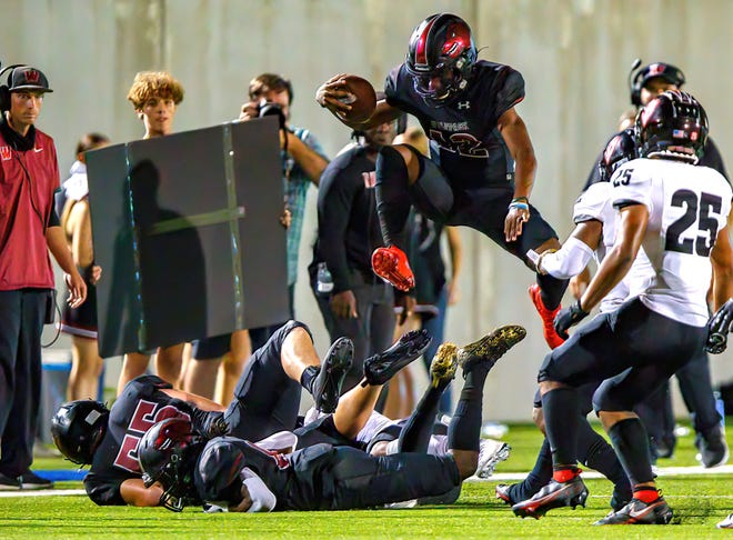 Weiss Wolves quarterback Dior Bradfield  hurdles over a pile for extra yardage against the Harker Heights Knights during the fourth quarter at the nondistrict football game on Aug. 27 at The Pfield. Harker Heights rode a dominant running game to a 43-35 win.