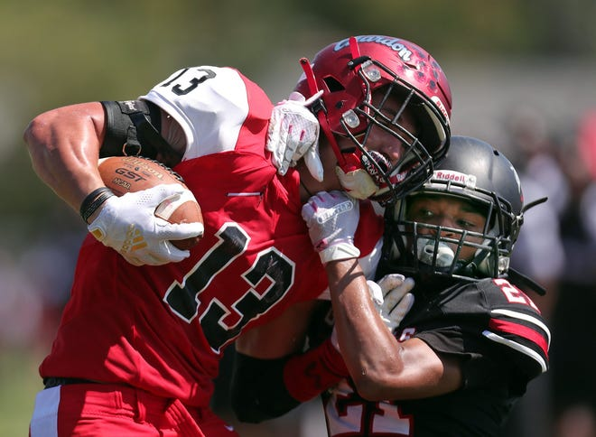 Buchtel defensive back Victor Jackson, right, brings down Chardon wide receiver Nathanael Sulka just short of the goal line during the Griffins' loss to the Hilltoppers on Saturday in Akron. [Jeff Lange/Beacon Journal]