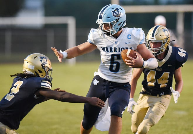 Central Valley quarterback Matt Merritt stiff-arms Knoch's Carson Kosecki (2), during Friday nightÕs game at Knoch High School.