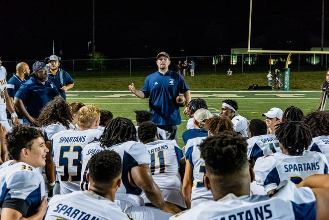 Battle coach Jonah Dubinski talks to his team after winning his first game as a head coach Friday night.