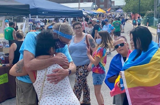 Delsie Bonaparte gets a free dad hug from Art Smith at Mid-Missouri Pridefest on Saturday.