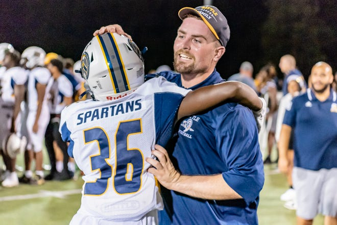 Battle head coach Jonah Dubinski hugs Damere Logan (36) on Friday night after getting his first victory leading the Spartans.