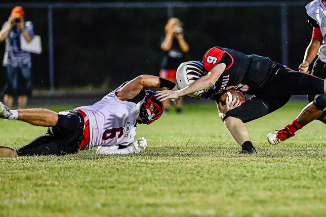 Senior linebacker Brock Ward, left, of the 2021 Chillicothe High School football Hornets completes a sack of a Marshall Owls quarterback during CHS' 27-8 season-opening victory at Marshall Friday, Aug. 27. The win was especially rewarding for Ward, who suffered an injury which effectively ended his junior season after less than a game in last year's clash with Marshall.