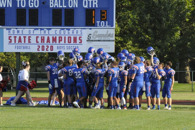 The Lenawee Christian football team celebrates after the unveiling of the 2020-21 Division 1 8-man state championship banner. [Telegram photo by Deloris Clark-Osborne]