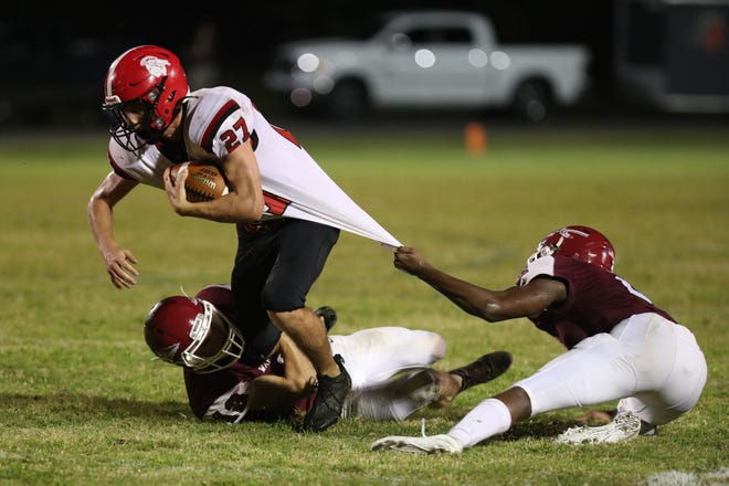 South Point's Ashton Harris tries to break an East Gaston tackle Friday night. The Red Raiders defeated the Warriors 35-7.