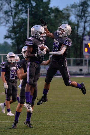 Ralph Rogers (45) and Murry Ross-Harman (17) celebrate a touchdown Friday night as Bloomington South hosted Martinsville.