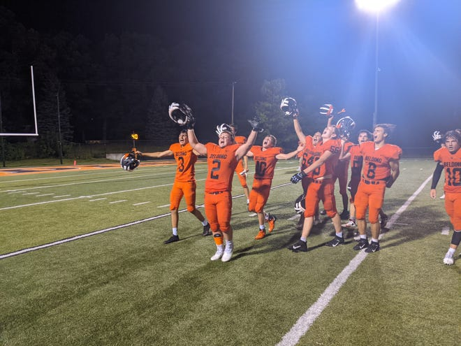 Belding's Franco Biella (3), Ethan Schmid (2) and Evan Williams (40) celebrate and acknowledge the crowd after the Black Knights beat Ionia 34-7 Friday night.