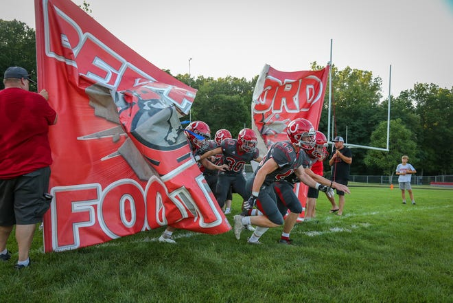 Gabe Johnson leads Bedford onto the field for the first football game of the season Friday night.