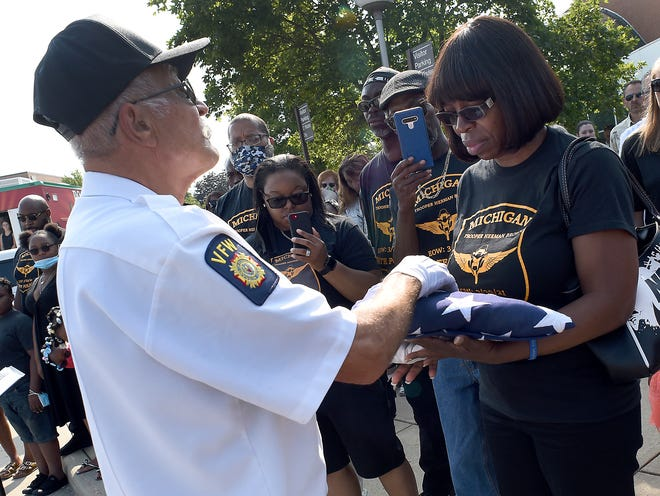 Bob Cebina post commander of Monroe Post 1138, Veterans of Foreign Wars presents the American Flag to Angela Allen of Detroit sister of the former Michigan State Police Trooper Herman Brown from the MSP Monroe Post who lost his life to COVID-19 this past March. The Celebration of Life service was held Saturday, August 28, 2021 at the La-Z-Boy Center, Meyer Theater at MCCC.