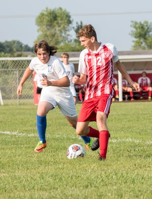 Logan Janes of Monroe (right) controls the ball as Cole Angerer of Ida chase a loose ball during Monroe's 6-0 victory Saturday.