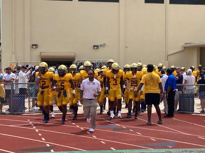 St. Thomas Aquinas coach Roger Harriott leads the Raiders onto the field for their game against St. Frances (Maryland) on Aug. 28, 2021 in Fort Lauderdale.