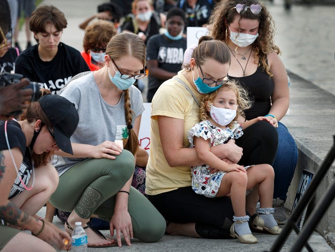 Protesters kneel in remembrance of George Floyd across the Intracoastal Waterway from Mar-a-Lago during the Declaration of Juneteenth Solidarity in West Palm Beach in June 2020. After the death of Floyd, a Minneapolis man who died at the hands of police in May, members of the Palm Beach County Criminal Justice Commission began holding town halls to address police reform issues. [LANNIS WATERS/palmbeachpost.com]