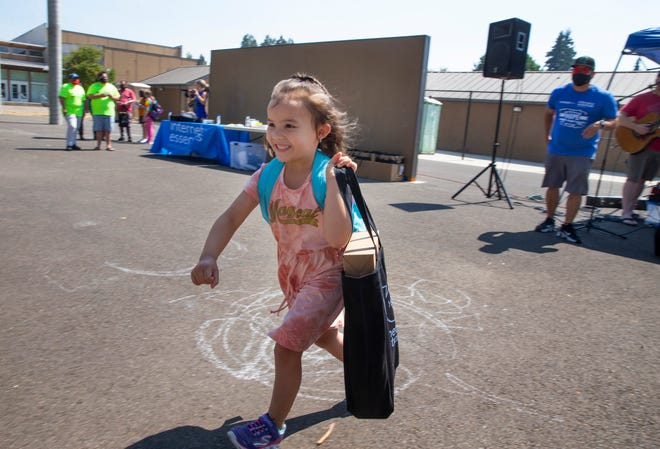 """Jonery Jaco, 5, races back to her family after receiving a new laptop at a """"Project Hope"""" event Saturday at Maple Elementary School in Springfield. Comcast and Onward Eugene joined """"Project Hope"""" to assist 3,000 Lane County-area school kids by supplying them with all the supplies they need to kick off a successful school year."""