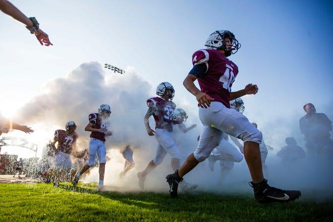 Mishawaka players run onto the field during the Mishawaka vs. Elkhart High School football game Friday, Aug. 27, 2021 at Mishawaka High School.