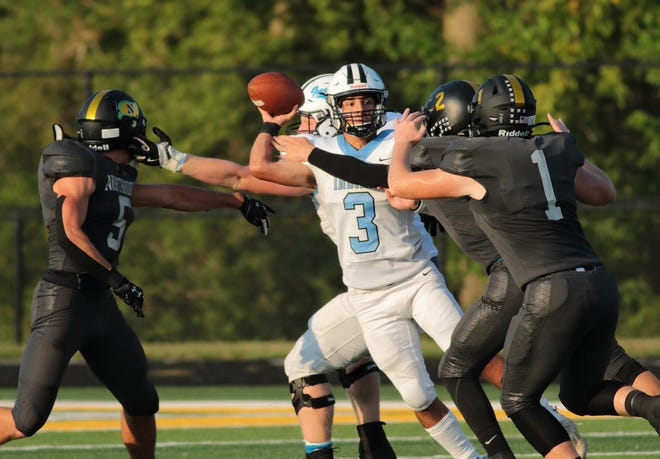 Saint Joseph quarterback Alex Ortiz (3), hunts for a receiver, under pressure from Northridge defenders Ridge Howard (5) and Peyton Shook (1)