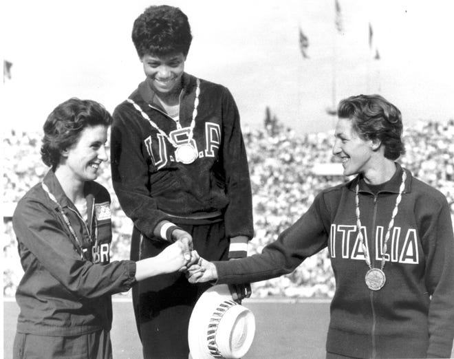 Gold medal winner Wilma Rudolph of the U.S., center, silver medalist Dorothy Hyman of Great Britain, left, and bronze medalist Giuseppina Leone of Italy share a three-way handshake at the victory stand during the XVI Summer Olympic Games in Rome on Sept. 2, 1960.   They competed in the women's 100-meter dash.