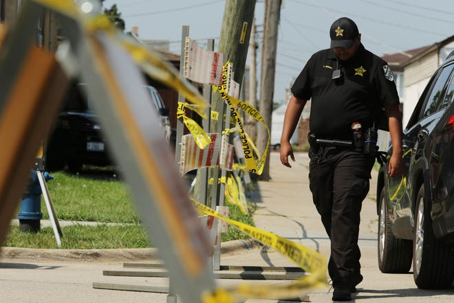 A police officer walks near the barricade along Center Avenue in Lyons, where authorities believe they've uncovered bodies in the backyard on Saturday, Aug. 28, 2021.