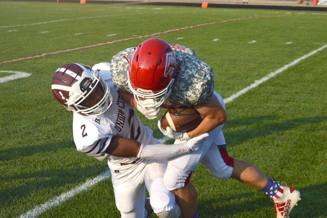 Constantine's Brayden Clark plows over a Union City defender as he runs for a big gain on Friday night.