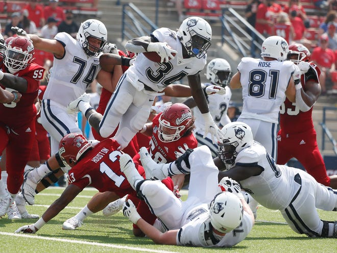 Connecticut running back Kevin Mensah (34) goes up for a short gain against Fresno State during the first half Saturday in Fresno, Calif.