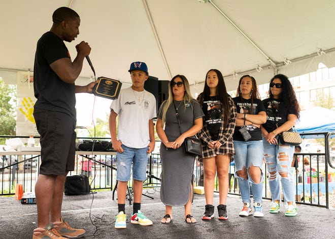 The family of fallen Worcester Police Officer Manny Familia receives the inaugural Adams Strong Award from Woodrow Adams Jr. at the 508 Forever Young event on Saturday in Worcester.