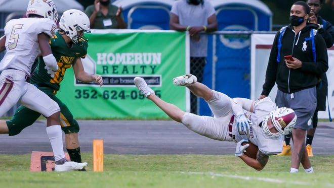 North Marion's Trent Hoffman (12) dives in for a touchdown Friday against Forest at Forest High School.