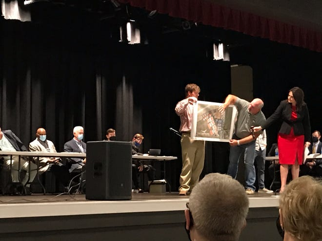 Trey Perman, Trent Thrasher and Christie Knowles, of the Etowah Community group, show a map of their proposed development for the Northeast Alabama Regional Airport at a public comment meeting held by the Gadsden Airport Authority.