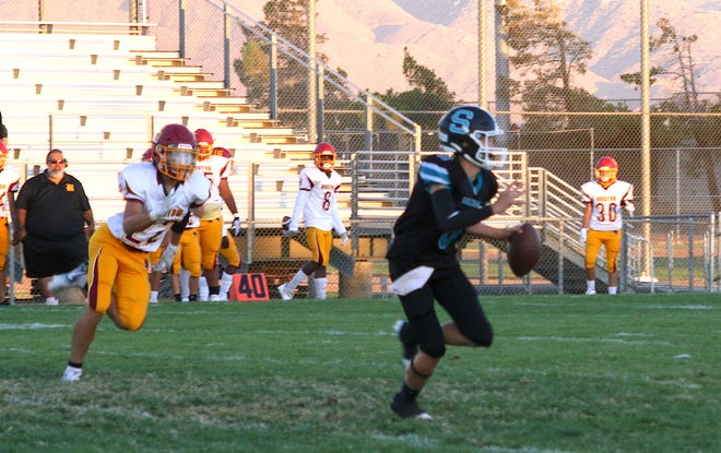 Sultana quarterback Jacob Higgs, a freshman, scrambles with the ball against Barstow at Jay Reed Stadium on Aug. 27, 2021.