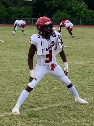 Miami Edison wide receiver Nathaniel Joseph stretches before playing at Deerfield Beach on Aug. 27, 2021