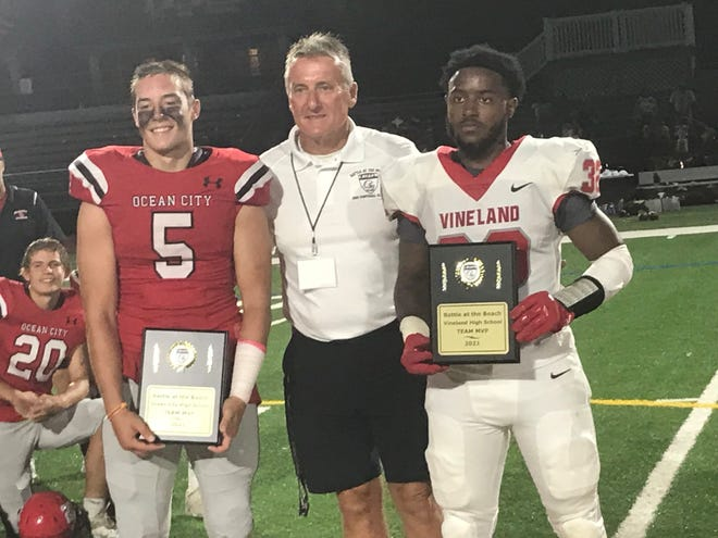 Ocean City's Sam Williams (left), Vineland's Nazhi Tatem (right) and Battle at the Beach director Clyde Folsom pose after Friday's game at Carey Stadium. The two players won MVP honors for their teams after Ocean City's 21-0 win over Vineland.