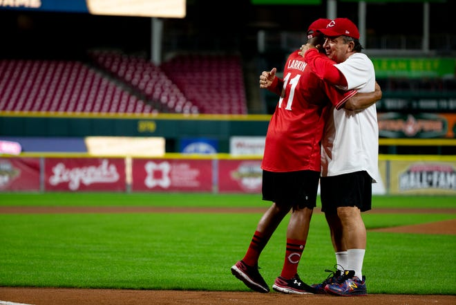 Former Reds players Barry Larkin (11) and Johnny Bench embrace after drawing an 8 in the sand for Joe Morgan before the Reds Legends softball game between Team Bench and Team Larkin involving former Reds players as part of the 2021 Reds Hall of Fame induction ceremony for Marty Brennaman on Friday, Aug. 27, 2021, at Great American Ball Park in Cincinnati.