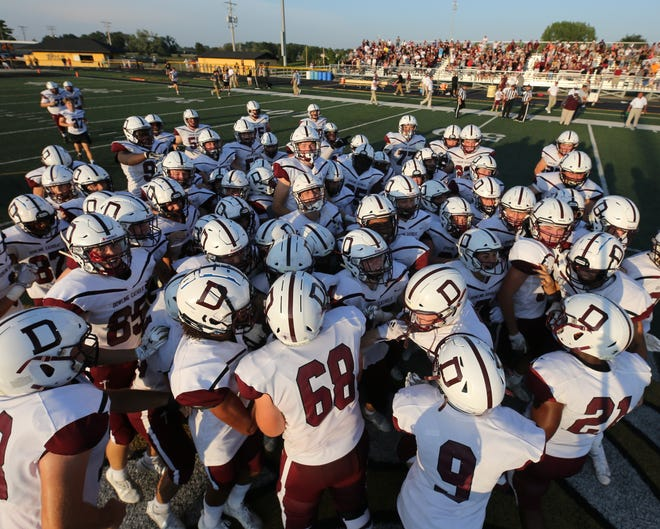 Dowling Catholic gathers on the field before their game against Southeast Polk at Southeast Polk High School on Friday, Aug. 27, 2021.