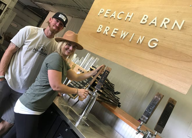 Jason and Sarah White pour a cold one from the tap at their Peach Barn Farmhouse and Brewery,  Sister Bay's first microbrewery.