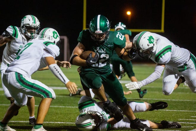 Fisher Catholic's Jack Tencza (22) powers through the Green Bobcat defense as the Fisher Catholic took on the Green Bobcats at Fulton Field in Lancaster, Ohio on August 27, 2021.