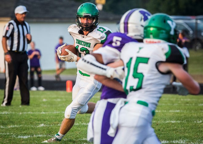 Yorktown's Kolton Nanko carries the football during a game against Muncie Central at Muncie Central High School Friday, Aug. 27, 2021.