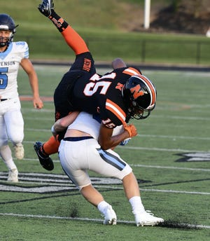 Northville wide receiver Kai Saunders gets tripped up by a Stevenson defender.