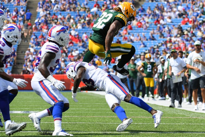 Green Bay Packers running back Kylin Hill (32) leaps over Buffalo Bills defensive back Siran Neal (33) while running with the ball during the second quarter at Highmark Stadium.