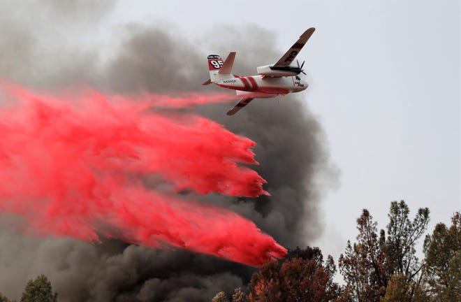 An air tanker drops retardant on a house fire at El Reno and Memory lanes in south Redding on Saturday, Aug. 28, 2021.