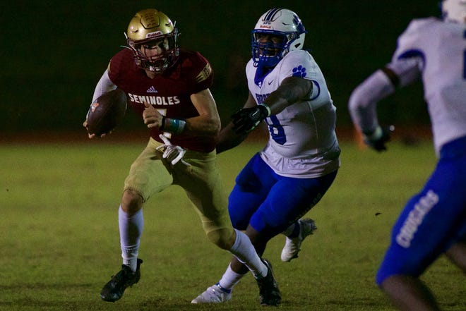 Senior quarterback Drew Faurot escapes a Godby defender in a game against the Cougars on Aug. 27 at Florida High.