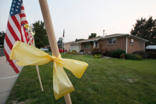 American flags and yellow ribbons line the sidewalk outside the house of Darren Hoover, whose son, Staff Sgt. Taylor Hoover was killed in Afghanistan, on August 27.