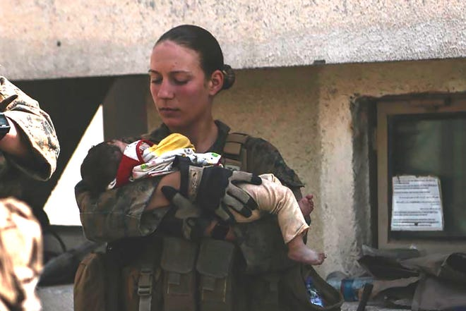 This undated photo provided by U.S. Department of Defense twitter page posted Aug. 20, 2021 shows Sgt. Nicole Gee holding a baby at Hamid Karzai International Airport in Kabul, Afghanistan.