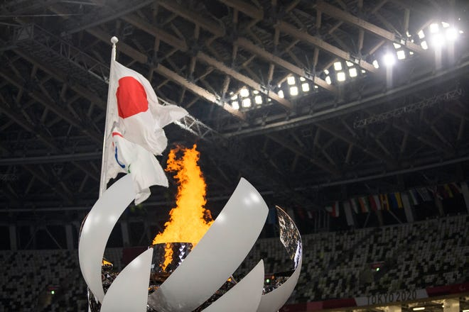The Japanese and the Paralympic flag fly behind the cauldron during the Tokyo Paralympic Games.