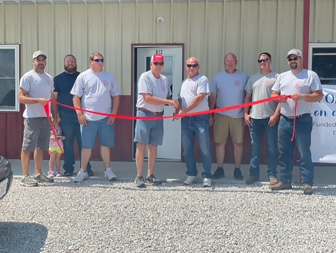 Picture C (ribbon cutting) left to right: Rob Rentel fire fighter, Kyle Stegner fire fighter, Drew Kammerich Assistant Chief, Gordon Shay Chief, Don Kammerich Deputy Chief, Terry Schupp fire fighter, Ryan Lorenz fire fighter, Keith Reuter fire fighter.