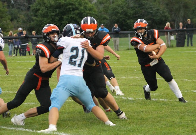 Cheboygan's Beau Ginop, right, looks to gain positive yardage while teammates block for him during Friday night's season-opening matchup against Petoskey at Western Avenue Field.