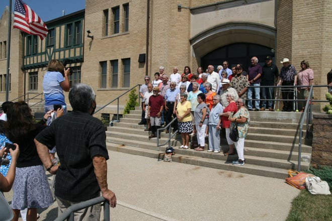 Photographer Vicki Schmucker takes a group portrait of those 70 or older who came to the Latino heritage project kickoff event Saturday at the Adrian Armory Events Center.
