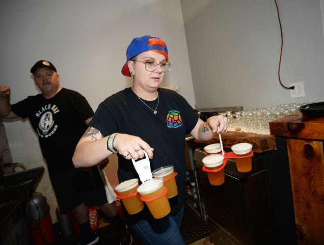 Shannon Kawa, right, serves beer at Black Hat Brew Works in Bridgewater on Saturday, Aug. 28, 2021.