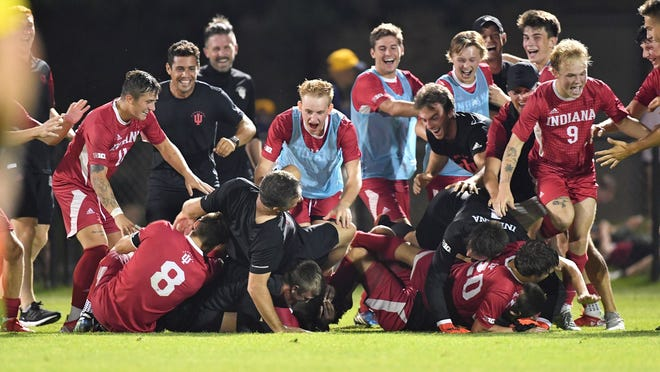 The Indiana men's soccer team celebrates Friday night's 3-2 overtime victory at Notre Dame with a dogpile on Ben Yeagley (20) as IU head coach Todd Yeagley, left, tumbles over the top. Ben Yeagley, bottom right, scored the game-winner, his first career goal as a Hoosier.