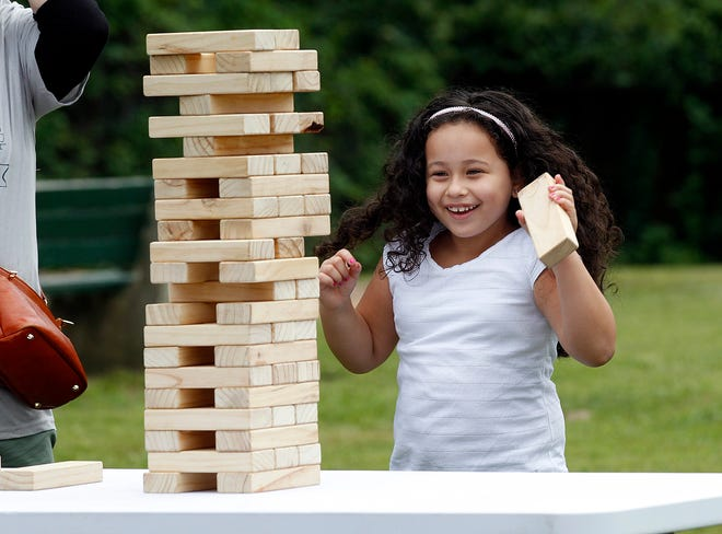 Maria Victoria, 5, an incoming kindergartner at the Harmony Grove Elementary School in Framingham, plays giant jenga during the renaming ceremony of the school, Aug. 28, 2021.